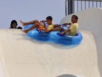 Aviator summer camp kids on a water slide