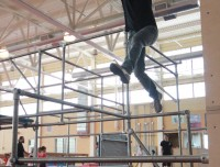 Man jumping between pipes while on a parkour course at Aviator Sports in Brooklyn