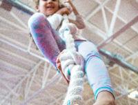 Girl climbs a gymnastics rope at summer sports camp