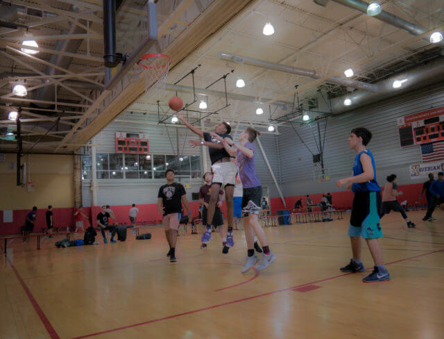 Teenagers playing basketball at Aviator's summer sports camp
