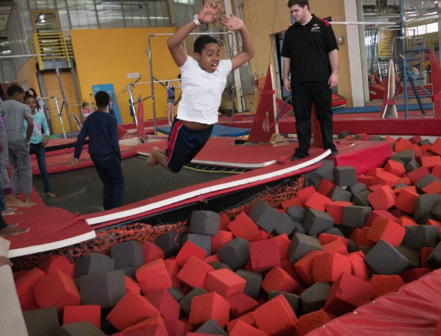 Boy jumping into a foam pit during summer break camp in Brooklyn