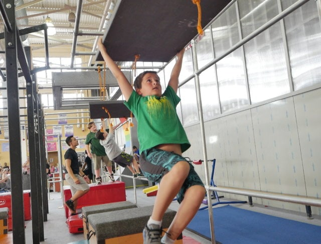 Boy tries the Aviator Sports Ninja Warrior parkour course