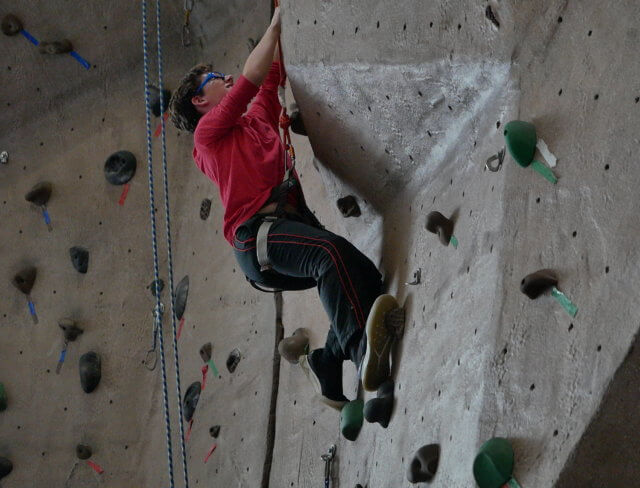 child climbing indoor rock wall in nyc