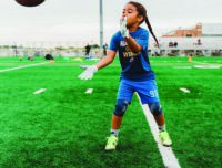 A girl about to catch a pass during a youth flag football game at Aviator Sports in Brooklyn