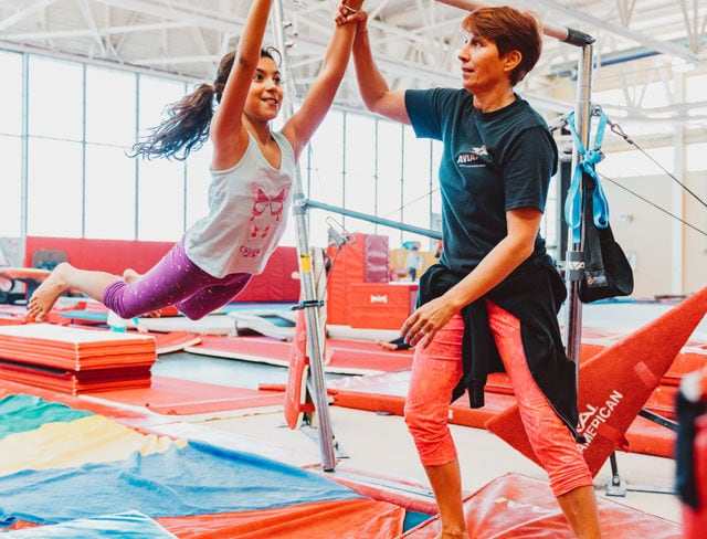 An instructor helps a girl on the bars in a gymnstics class