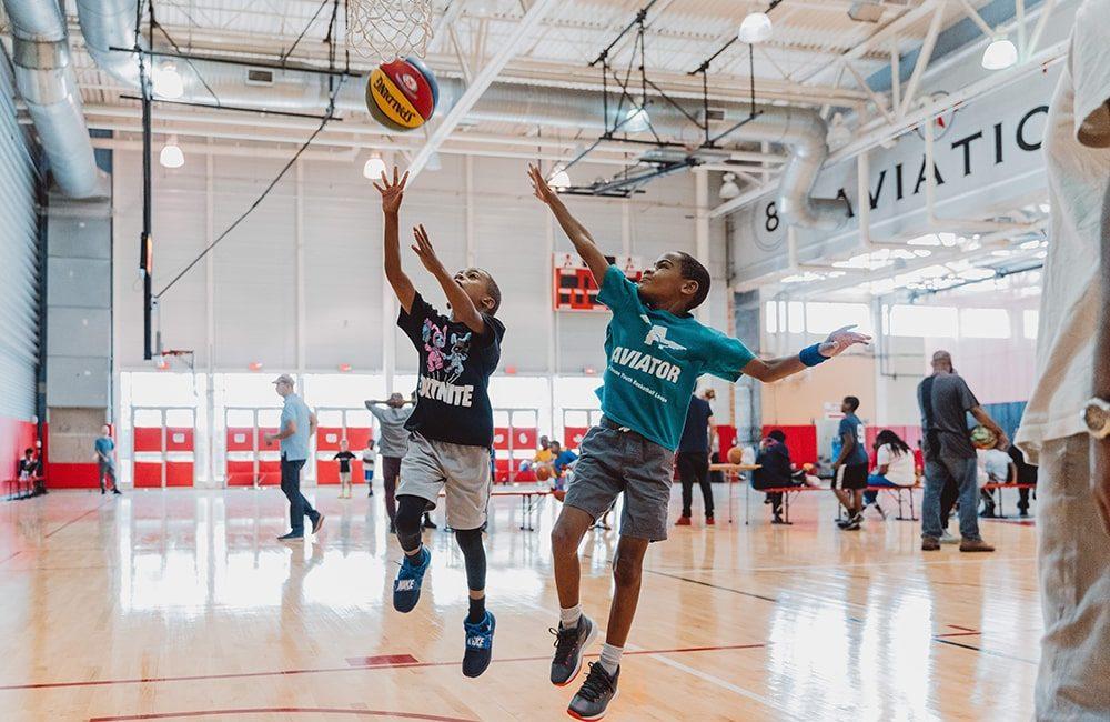 A boy shoots a basketball in a kids basketball league