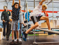 Boy jumps a pole learning parkour for kids at Aviator Sports in Brooklyn