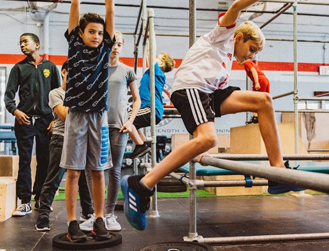 Boy jumps a pole learning parkour at Aviator Sports in Brooklyn