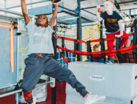 Boy does the rings as part of a Ninja Warrior course