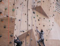 Two adult rock climb during a Chancellor's Day event