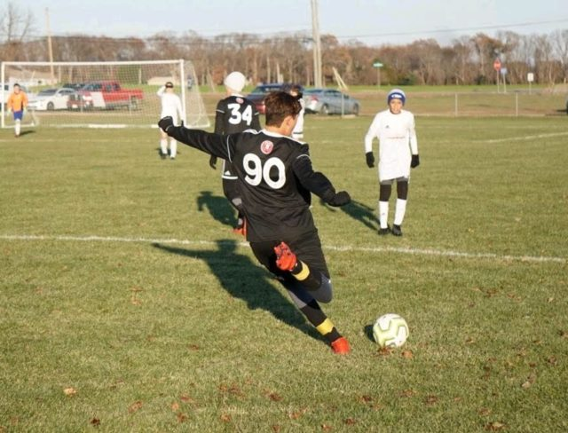 kid kicking a soccer ball in youth soccer clinics